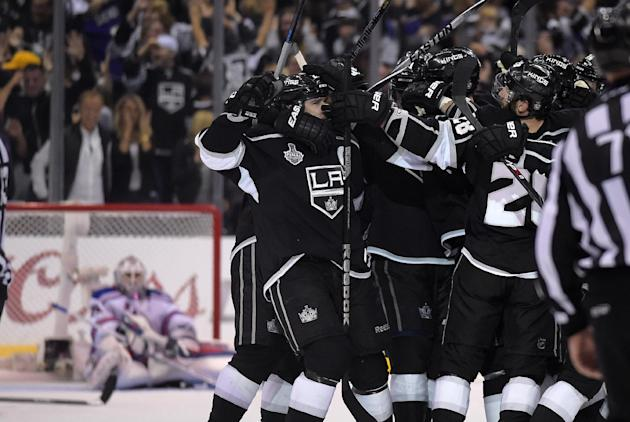 Members on the Los Angeles Kings, right, celebrates a game-winning goal by right wing Dustin Brown as New York Rangers goalie Henrik Lundqvist, left, of Sweden, looks on in the second overtime period in Game 2 of the NHL hockey Stanley Cup Finals, Saturday, June 7, 2014, in Los Angeles. The Kings won 5-4. (AP Photo/Mark J. Terrill)