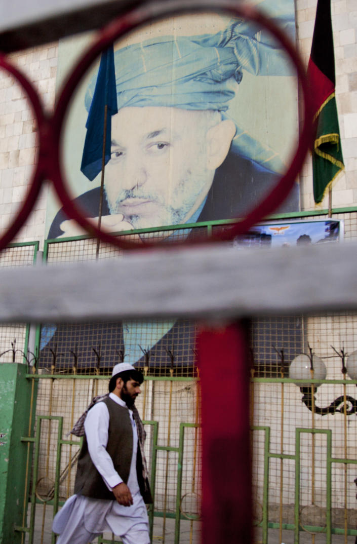 An Afghan man passes by a giant poster of Afghanistan's President Hamid Karzai in the center of Kabul, Afghanistan, Wednesday, Oct 31, 2012. Presidential elections considered crucial to Afghanistan's security and stability will be held on schedule in April 2014, the country's election commission announced Oct 31. The decision eased concerns that President Hamid Karzai would seek to delay the election despite his repeated assurances that he would not. (AP Photo/Anja Niedringhaus)