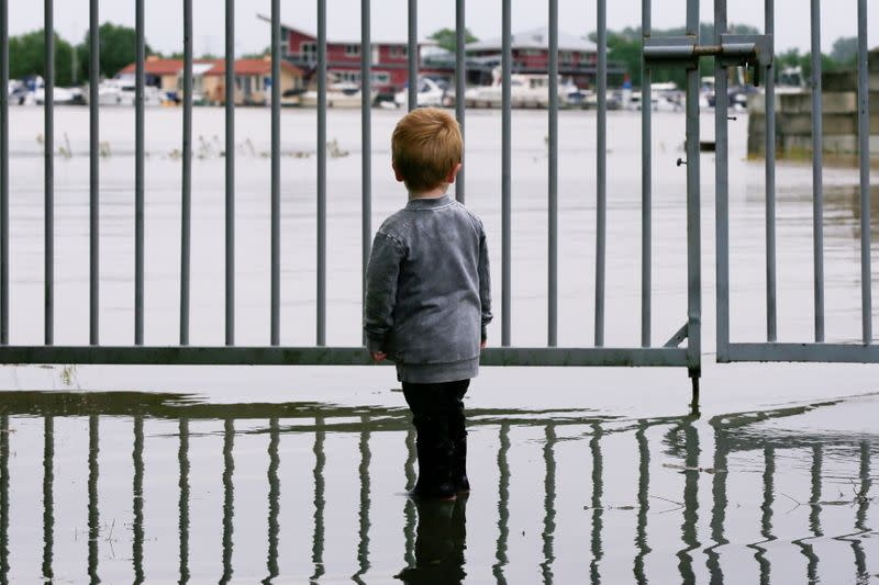 FILE PHOTO: A child looks on as water floods through a fence in Wessem