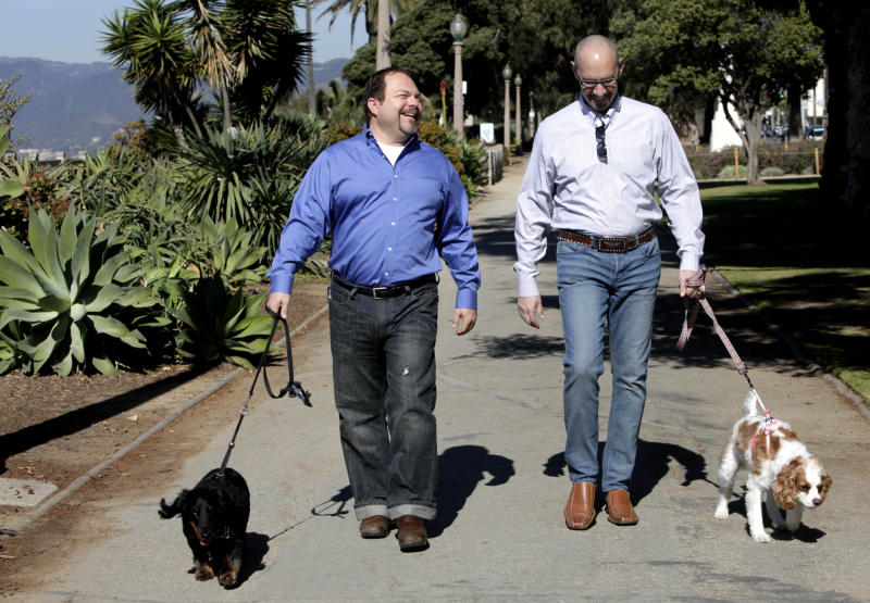 This Feb. 23, 2012 photo shows Steven May, right walking with his dog, Winnie beside his attorney, David Pisarra, walking his dog, Dudley in Santa Monica, Calif. Custody cases involving pets are on the rise across the country. In a 2006 survey by the 1,600-member American Academy of Matrimonial Lawyers, a quarter of respondents said pet custody cases had increased noticeably since 2001. (AP Photo/Nick Ut)