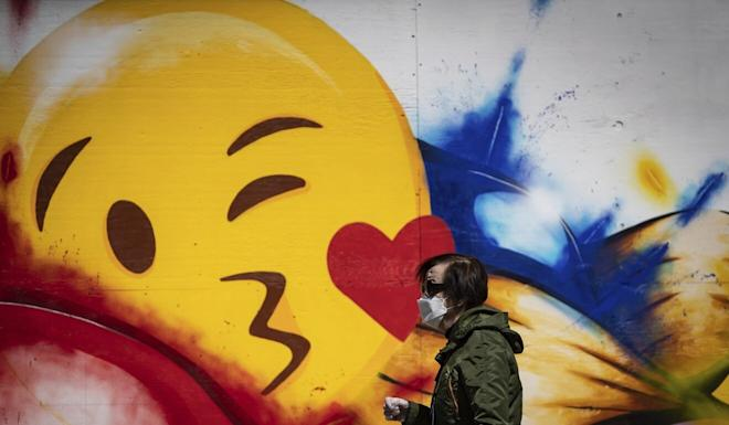 A woman wearing a face mask and gloves walks past a large emoji face painted on the boarded windows of a store in Vancouver, British Columbia, on May 6. Photo: AP