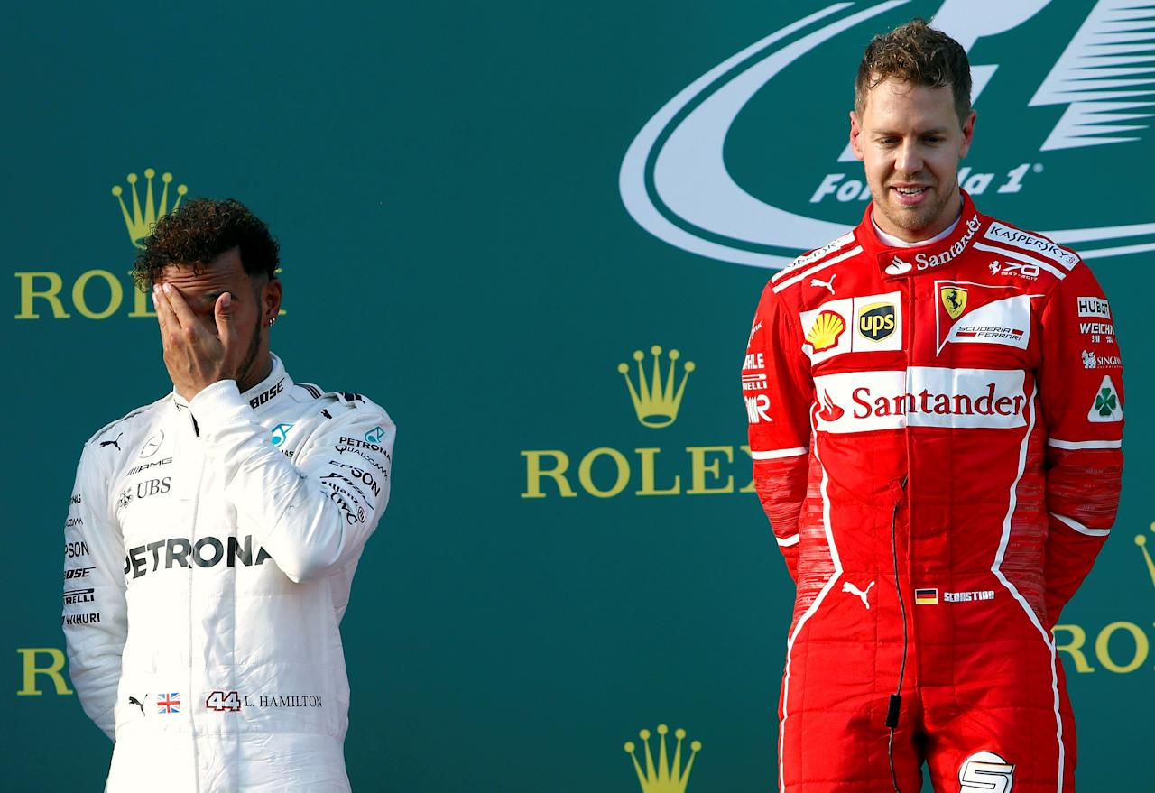 Formula One - F1 - Australian Grand Prix - Melbourne, Australia - 26/03/2017 - Ferrari driver Sebastian Vettel of Germany stands next to Mercedes driver Lewis Hamilton of Britain after winning the Australian Grand Prix.     REUTERS/Brandon Malone