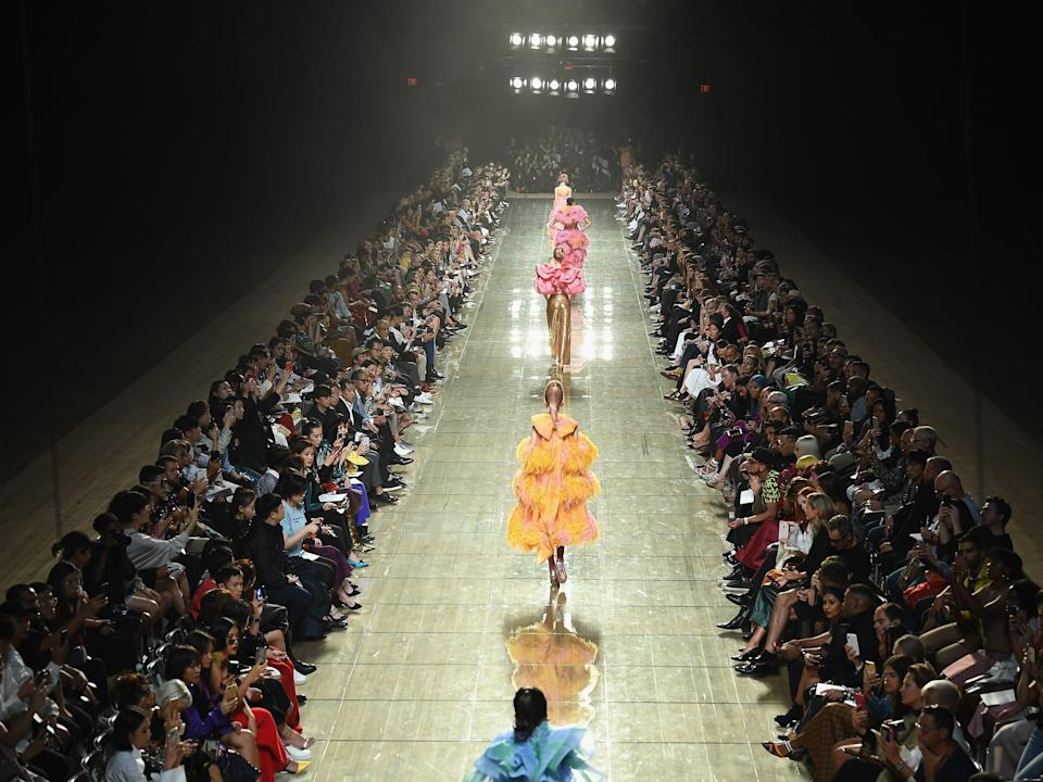Models walk down a runway surrounded by spectators at a Marc Jacob fashion show.