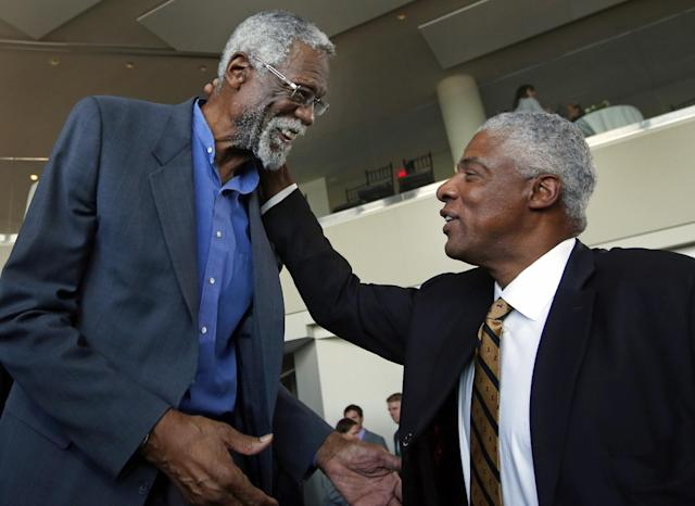 Julius Erving, right, former Philadelphia 76ers basketball great, greets former Boston Celtics basketball star Bill Russell after a statue honoring Russell was unveiled at City Hall Plaza in Boston, Friday, Nov. 1, 2013. (AP Photo/Elise Amendola)