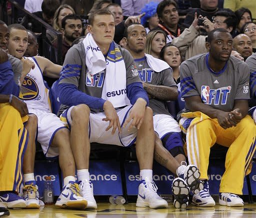 Golden State Warriors starters, from left, Stephen Curry (30), Andris Biedrins, Monta Ellis, and rookie Charles Jenkins watch from the bench during the second half of an NBA basketball game against the Sacramento Kings Tuesday, Jan. 31, 2012, in Oakland, Calif. (AP Photo/Ben Margot)