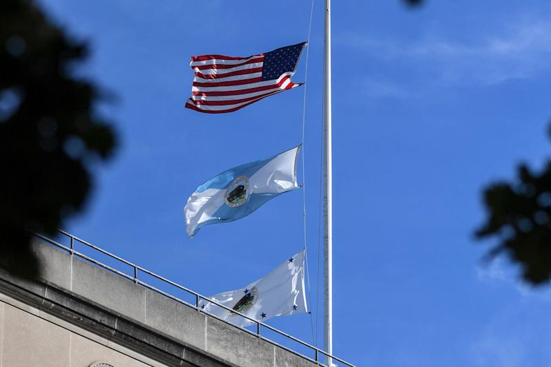 The flag for the Interior Department's deputy secretary, bottom, flies above agency headquarters in Washington. The middle flag represents the department.
