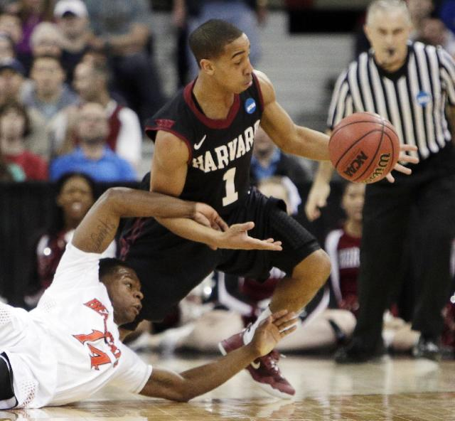 Harvard's Siyani Chambers (1) and Cincinnati's Ge'Lawn Guyn (14) fight for a loose ball in the second half during the second-round of the NCAA college basketball tournament in Spokane, Wash., Thursday, March 20, 2014. (AP Photo/Young Kwak)