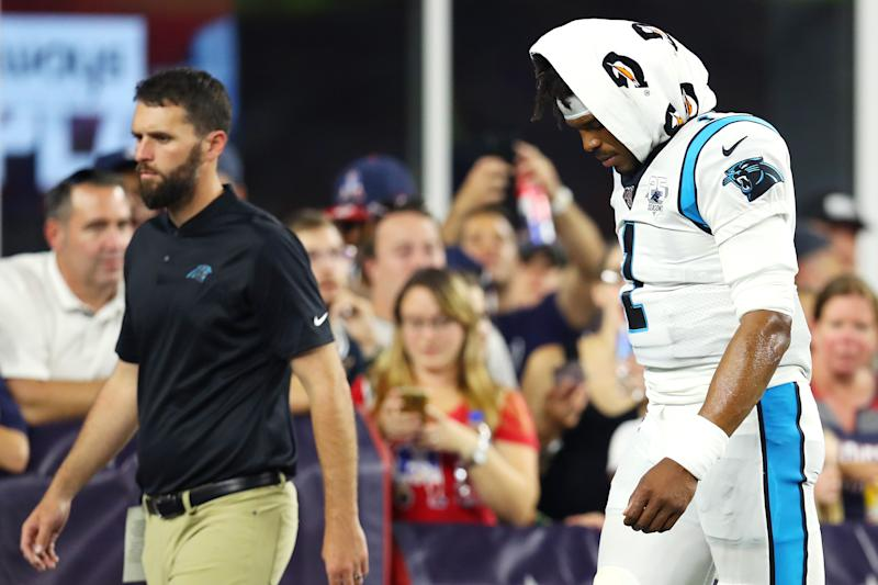 Cam Newton exits the field after suffering a foot injury against the Patriots. (Getty Images)