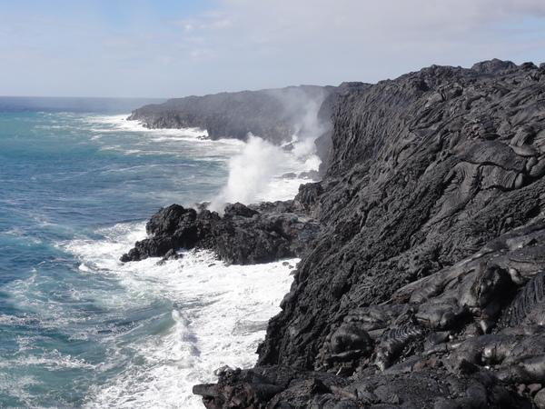 Lava from Kilauea volcano in Hawaii drops into the ocean. Steam plumes rise where the hot molten rock meets the sea.