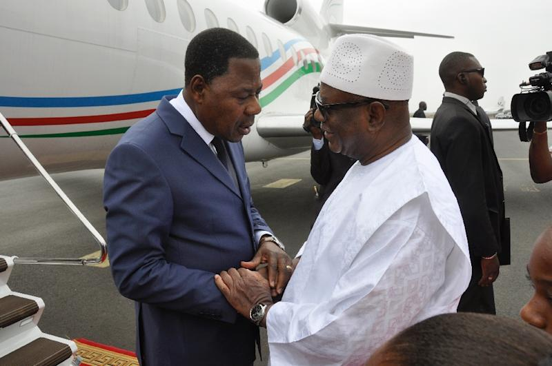 Mali's President Ibrahim Boubacar Keita (R) speaks with Benin's President Thomas Yayi Boni (L) upon his arrival in Bamako on November 23, 2015, two days after a deadly attack (AFP Photo/Habibou Kouyate)