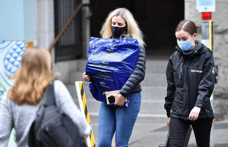 People are seen wearing protective face masks during lockdown in Brisbane.