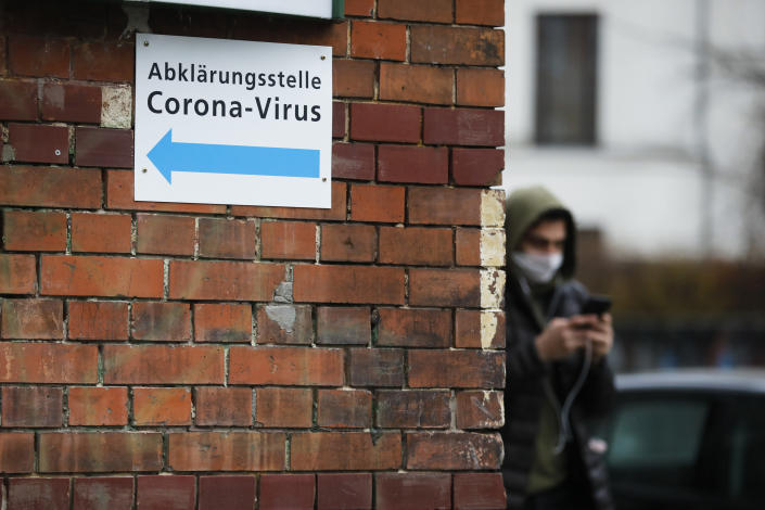 A man with a mask pass an information sign directing to a new set up test and information centre for the new coronavirus at the district Prenzlauer Berg in Berlin, Germany, Monday, March 9, 2020 (AP Photo/Markus Schreiber)