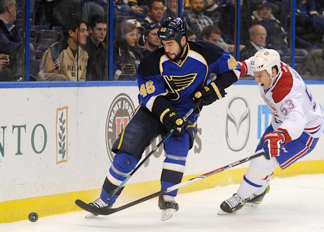 St. Louis Blues' Roman Polak (46), of the Czech Republic, and Montreal Canadiens' Ryan White (53) reach for the puck during the first period of an NHL hockey game on Thursday, Dec. 19, 2013, in St. Louis. (AP Photo/Bill Boyce)