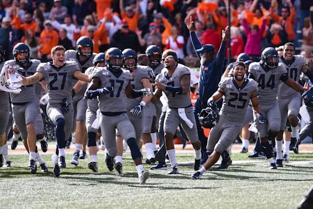 The Illinois team runs onto the field after kicking the game-winning field goal to beat 6th-ranked Wisconsin, 24-23, on Saturday. (Getty)
