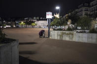 A homeless woman looks for food in the empty center of Lyon, central France, Saturday, Oct. 17, 2020. France is deploying 12,000 police officers to enforce a new curfew that came into effect Friday night for the next month to slow the virus spread, and will spend another 1 billion euros to help businesses hit by the new restrictions. (AP Photo/Laurent Cipriani)