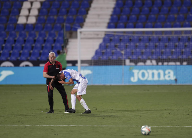 Leganes' head coach Javier Aguirre, left, tries to comfort his player Jonathan Silva, after the Spanish La Liga soccer match between Leganes and Real Madrid at the Butarque Stadium in Leganes, on the outskirts of Madrid, Spain, Sunday, July 19, 2020. The match ended 2-2 draw, and Leganes are being relegated from La Liga to the second division. (AP Photo/Bernat Armangue)