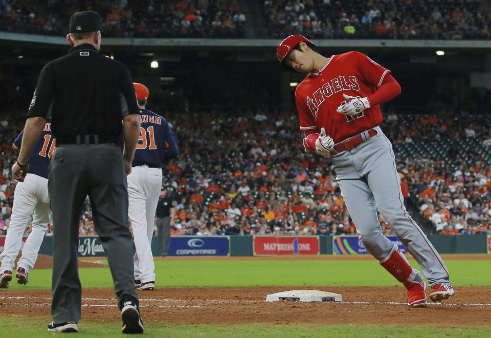 Los Angeles Angels' Shohei Ohtani, right, grounds out to first base in the eighth inning of a baseball game against the Houston Astros, Sunday, Sept. 23, 2018, in Houston. (AP Photo/Richard Carson)