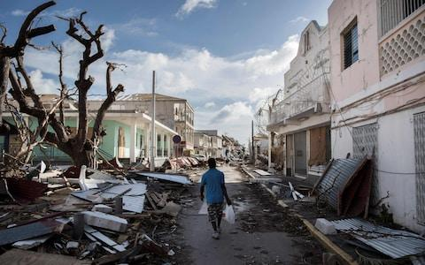 A man walks on a street covered in debris after hurricane Irma hurricane passed on the French island of Saint-Martin, near Marigot - Credit:  MARTIN BUREAU