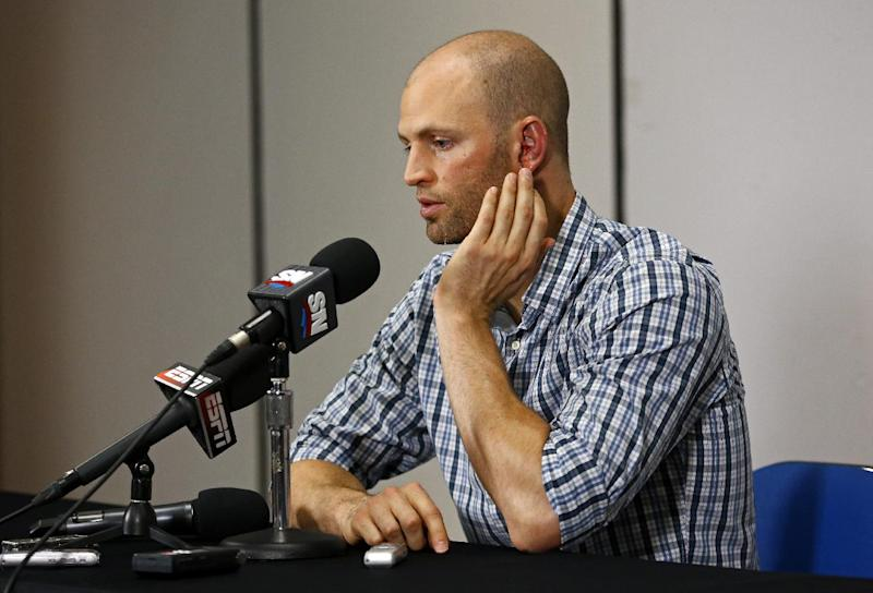 Toronto Blue Jays pitcher J.A. Happ gestures to his head during a press conference before a baseball game against the Tampa Bay Rays Wednesday, May 8, 2013, in St. Petersburg, Fla. Happ was speaking following his release from the hospital earlier in the day, after being hit by a line drive from Tampa Bay Rays' Desmond Jennings the previous night.  (AP Photo/Mike Carlson)