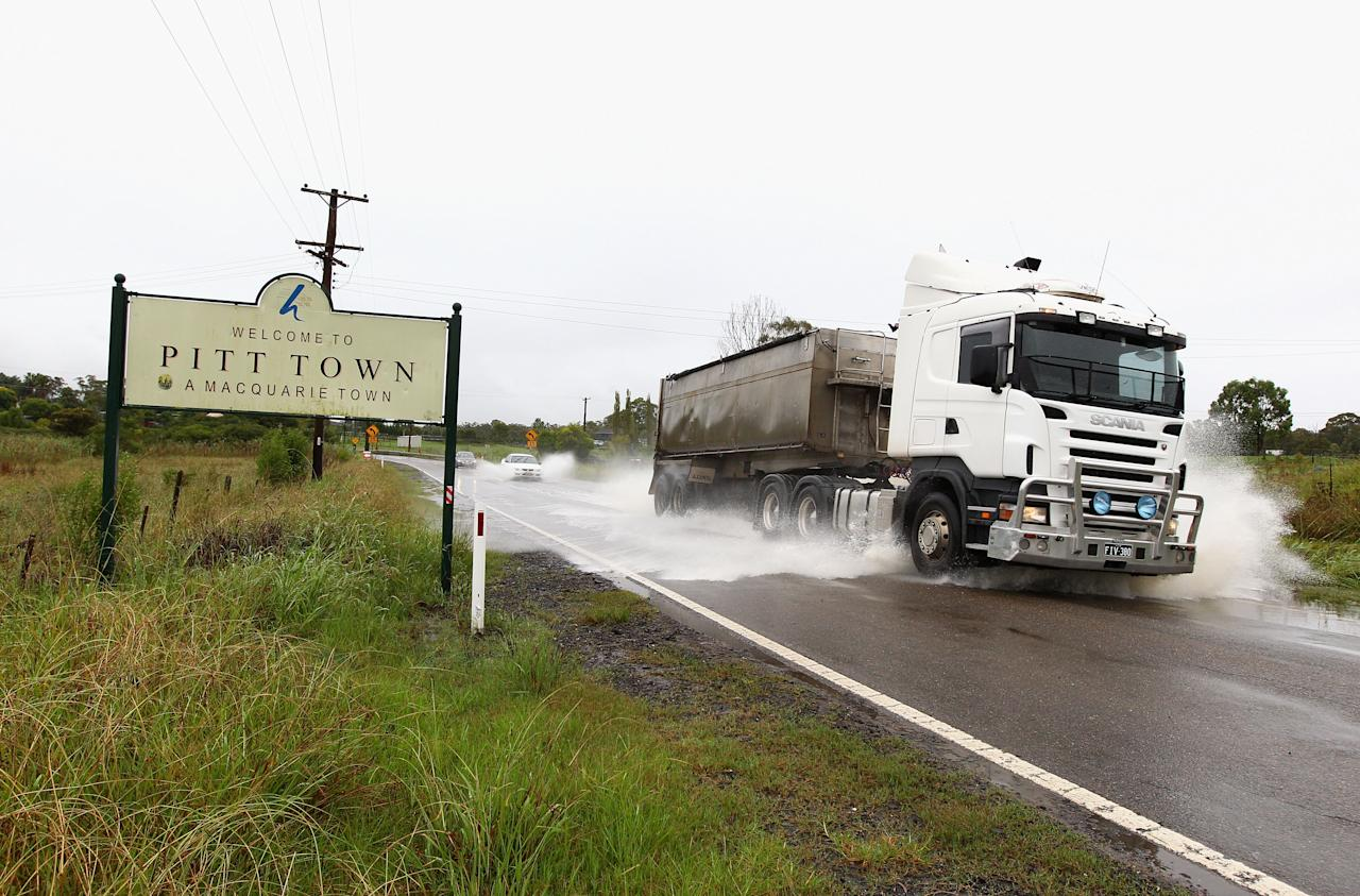RICHMOND, AUSTRALIA - MARCH 02:  A truck drives through flood waters in Pitt Town on March 2, 2012 near Richmond, Australia. Over 1000 people have been evacuated as record rainfall continues across at least three quarters of the state of NSW. Sydney and surrounding areas experienced one of the wettest and coolest summers in many years, which looks set to continue into March.  (Photo by Ryan Pierse/Getty Images)