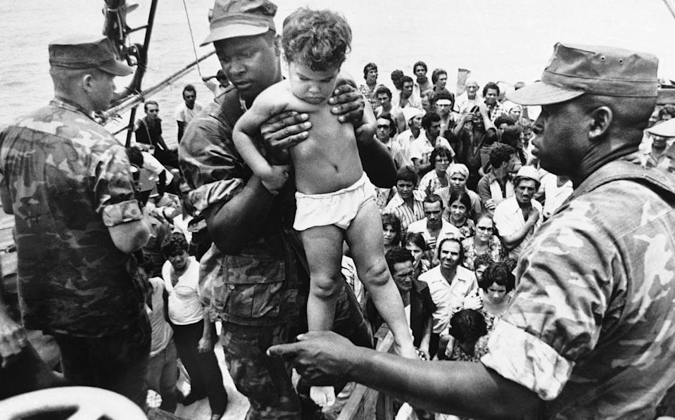 A U.S. Marine in uniform helps a Cuban toddler dressed only in a diaper off a boat.