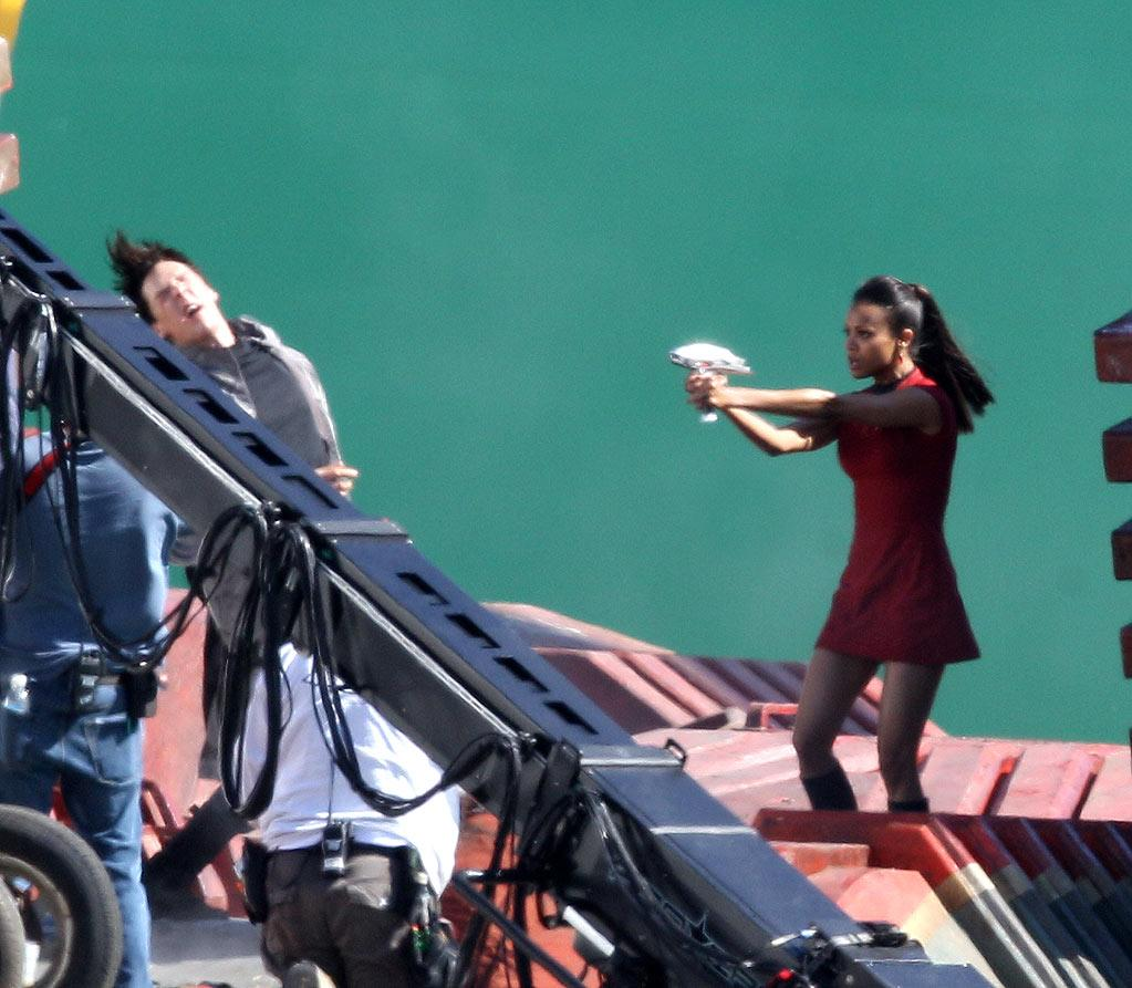 The first images from the set of the highly anticipated Untitled Star Trek Sequel. Zoe Saldana as Nyota Uhura uses a Phaser Gun to save Spock from a Villain on a space cargo ship.