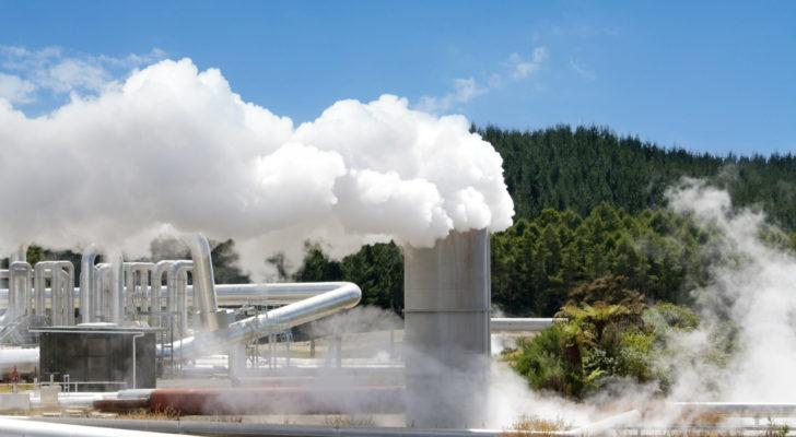 A geothermal power plant operates with a forest and a clear, bright sky visible behind it.
