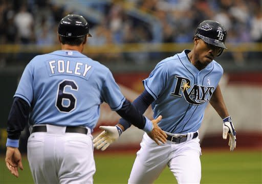 Tampa Bay Rays' B.J. Upton, right, slaps hands with third base coach Tom Foley while rounding the bases after hitting a solo home run off Miami Marlins starting pitcher Josh Johnson during the first inning of an interleague baseball game on Sunday, June 17, 2012, in St. Petersburg, Fla. (AP Photo/Brian Blanco)