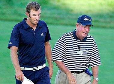 A PGA of America rules official chats with Dustin Johnson (L) on the 18th green during the final round