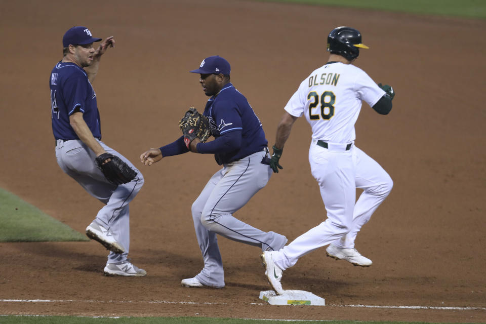 Tampa Bay Rays' Yandy Diaz, center, puts out Oakland Athletics' Matt Olson, right, as Rich Hill watches during the sixth inning of a baseball game in Oakland, Calif., Friday, May 7, 2021. (AP Photo/Jed Jacobsohn)