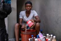 A gasoline street vendor pours gasoline from a bucket into used soft drink bottles following the assassination of President Jovenel Moise, in Port-au-Prince