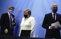 German Chancellor Angela Merkel, centre, Markus Soder, Prime Minister of Bavaria and CSU Chairman, left and Peter Tschentscher, the First Mayor of Hamburg, leave after a press conference, in Berlin, Tuesday, Sept. 29, 2020. Chancellor Angela Merkel and the governors of Germany's 16 states conferred on how to prevent the country's coronavirus infection figures from accelerating to the levels being seen in other European countries. (Kay Nietfeld/dpa via AP)