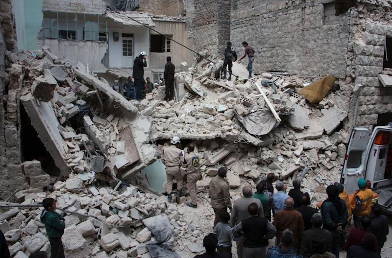 People inspect a destroyed building following a reported air strike by government forces on the rebel held area in the east of the northern Syrian city of Aleppo on April 13, 2015 (AFP Photo/Karam Al-Masri)
