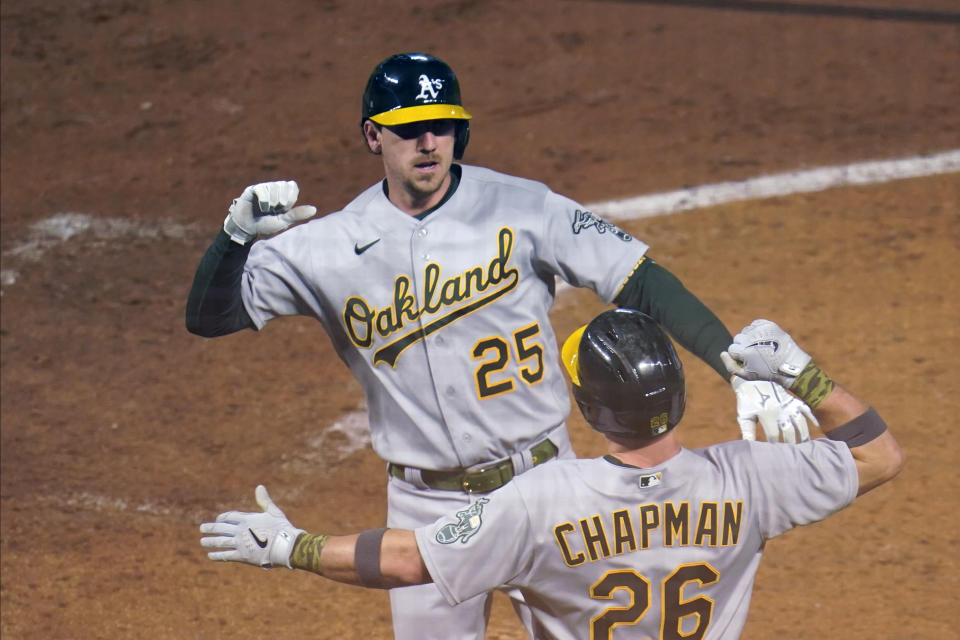 Oakland Athletics' Stephen Piscotty, top, celebrates his two-run home run off Minnesota Twins pitcher Matt Shoemaker with Matt Chapman during the sixth inning of a baseball game Friday, May 14, 2021, in Minneapolis. (AP Photo/Jim Mone)