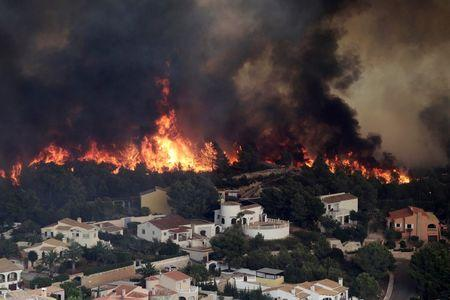 Flames of a wildfire engulf a hillside next to houses in Benitatxell near Alicante, Spain September 5, 2016. REUTERS/Heino Kalis