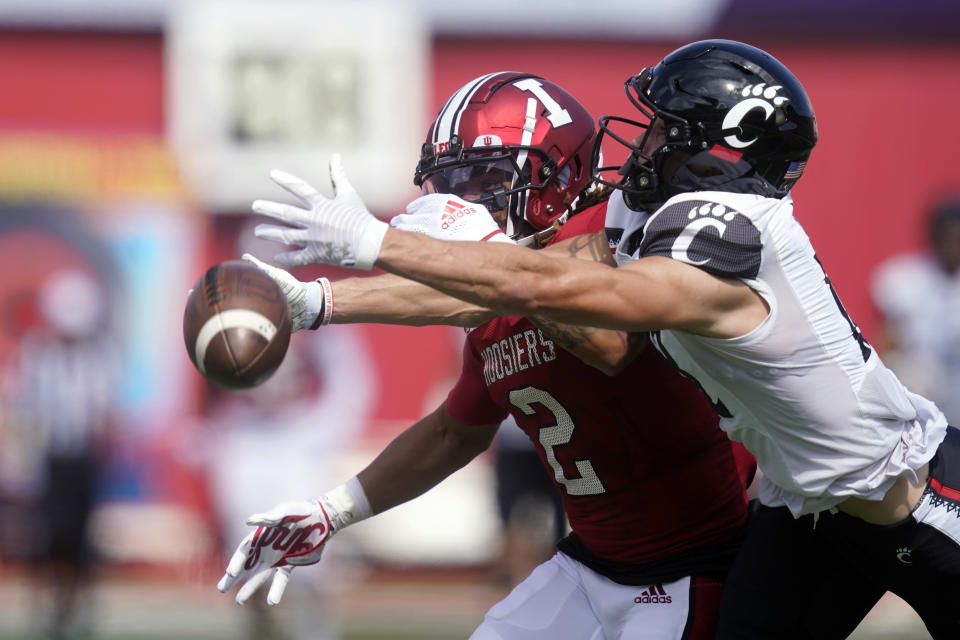 Cincinnati's Alec Pierce (12) tries to make a catch against Indiana's Reese Taylor (2) during the first half of an NCAA college football game, Saturday, Sept. 18, 2021, in Bloomington, Ind. (AP Photo/Darron Cummings)