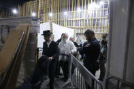 Ultra-Orthodox Jewish men leave a synagogue in Givat Zeev, outside Jerusalem, Sunday, May 16, 2021. Israeli medics say more than 150 people were injured in a fatal collapse of a bleacher at an uncompleted West Bank synagogue. (AP Photo/Sebastian Scheiner)