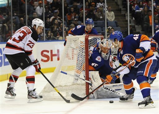 New York Islanders goalie Anders Nilsson (45) and Dylan Reese (42) defend against New Jersey Devils' David Clarkson (23) in the second period of an NHL hockey game on Saturday, March 10, 2012, in Uniondale, N.Y. (AP Photo/Kathy Kmonicek)
