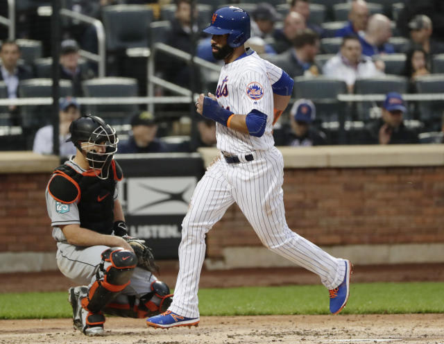 New York Mets' Jose Bautista runs past Miami Marlins catcher J.T. Realmuto to score on a sacrifice fly ball during the second inning of a baseball game Tuesday, May 22, 2018, in New York. (AP Photo/Frank Franklin II)