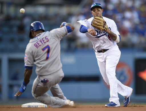 Los Angeles Dodgers shortstop Manny Machado, right, throws to first after forcing out New York Mets' Jose Reyes to complete a double play during the fifth inning of a baseball game in Los Angeles, Monday, Sept. 3, 2018. Jeff McNeil was forced out at first base. (AP Photo/Kelvin Kuo)