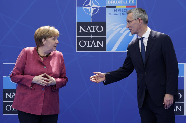 German Chancellor Angela Merkel speaks with NATO Secretary General Jens Stoltenberg as they pose for photos at the NATO summit at NATO headquarters in Brussels, Monday, June 14, 2021. (AP Photo/Patrick Semansky, Pool)