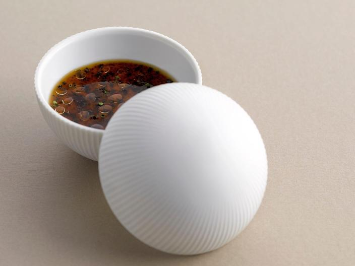 """Chef Andre Chiang's classic """"memory"""" dish is served in a white bowl with a white lid."""