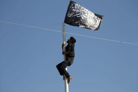 FILE PHOTO: A member of Nusra Front climbs a pole where a Nusra flag waves in the town of Ariha in Syria's Idlib province