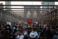 Demonstrators march across the Brooklyn Bridge as they remember George Floyd on the one-year anniversary of his death, Tuesday, May 25, 2021, in New York. (AP Photo/Eduardo Munoz Alvarez)