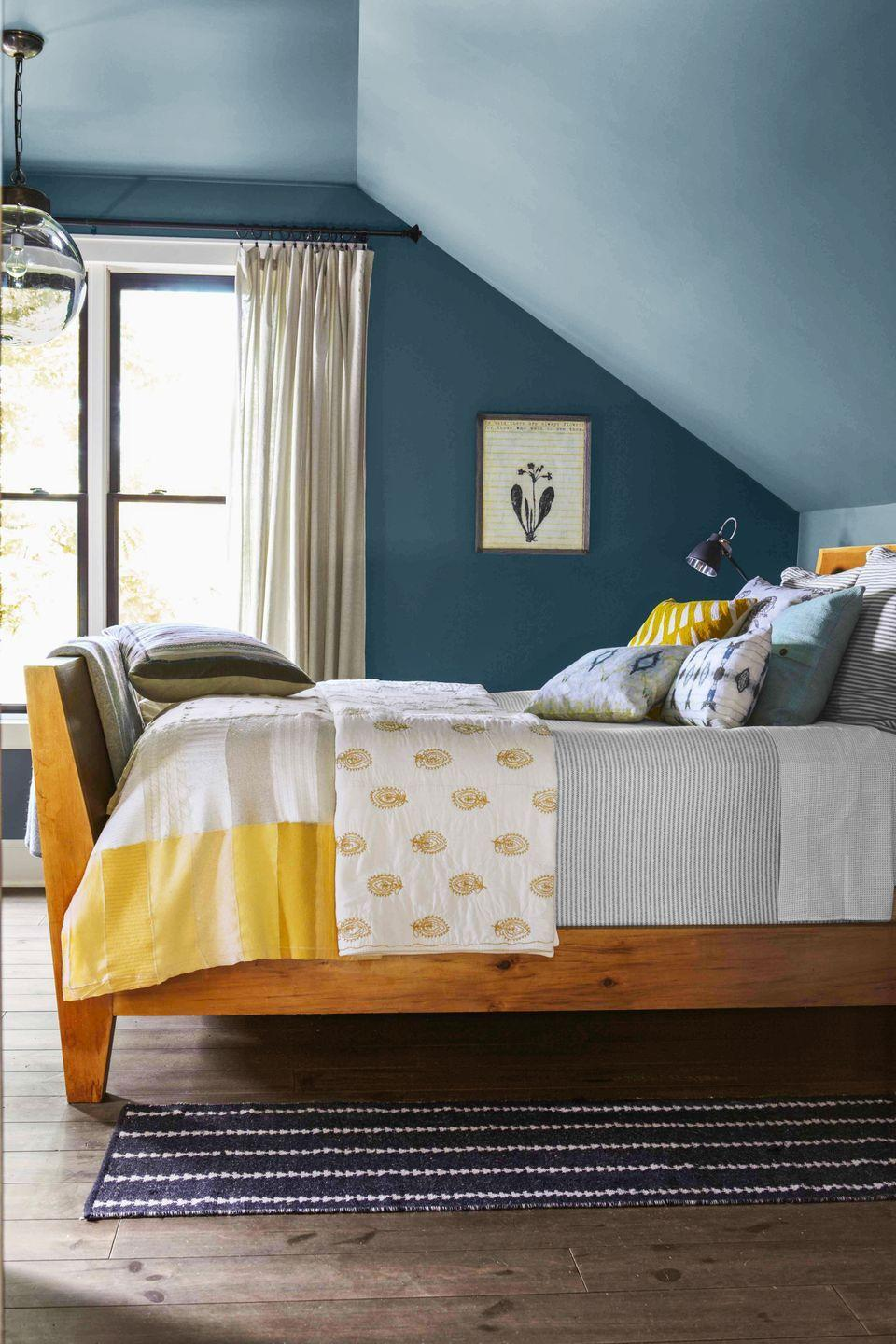 <p>Extending paint from the walls up onto the eaves and overhead makes this top-floor room extra cozy. The blue hue and yellow bedding prove opposites attract too. </p>