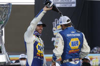 Chase Elliott, left, and pit crew chief Alan Gustafson celebrate their season championship in Victory Lane after winning a NASCAR Cup Series auto race at Phoenix Raceway, Sunday, Nov. 8, 2020, in Avondale, Ariz. (AP Photo/Ralph Freso)