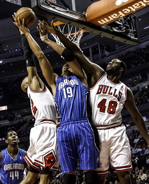 Chicago Bulls' Taj Gibson (22) and Nazr Mohammed (48) put defensive pressure on Orlando Magic's Gustavo Avon during an NBA basketball game in Chicago on Tuesday, Nov. 6, 2012.(AP Photo/Charles Cherney)