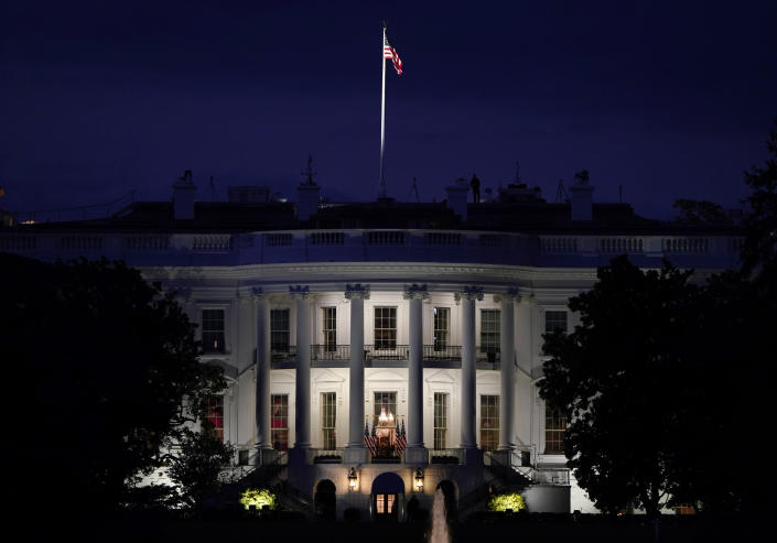 FILE - In this Oct. 5, 2020, file photo an American flag files atop the White House after President Donald Trump arrived from Walter Reed National Military Medical Center via Marine One in Washington. (AP Photo/J. Scott Applewhite, File)