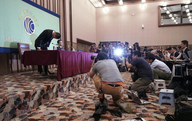 Nihon University's American football player Taisuke Miyagawa, left, bows at a news conference Tuesday, May 22, 2018, in Tokyo. The Japanese college football player has apologized for intentionally injuring the quarterback of an opposing team, an incident that has riveted Japan for several weeks. In a news conference broadcast live across Japan, Miyagawa bowed deeply and said his coach had told him to do it - but he said he should have been stronger and refused the coaching order. (AP Photo/Eugene Hoshiko)