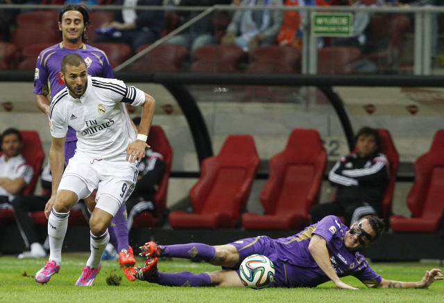 Real Madrid's Karim Benzema from France, left, and Fiorentina's Gonzalo Rodriguez challenge for the ball during their friendly soccer match in Warsaw, Poland, Saturday, Aug. 16, 2014.(AP Photo/Czarek Sokolowski)